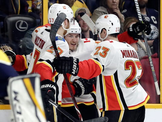 Calgary Flames left wing Matthew Tkachuk, center, celebrates with Dougie Hamilton (27) and Sean Monahan (23) after scoring a goal against the Nashville Predators in the first period of an NHL hockey game Thursday, Feb. 15, 2018, in Nashville, Tenn. (AP Photo/Mark Humphrey)