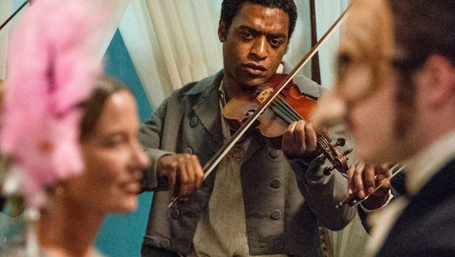 """This image released by Fox Searchlight shows Chiwetel Ejiofor, center, in a scene from """"12 Years A Slave."""" (AP Photo/Fox Searchlight, Jaap Buitendijk)"""