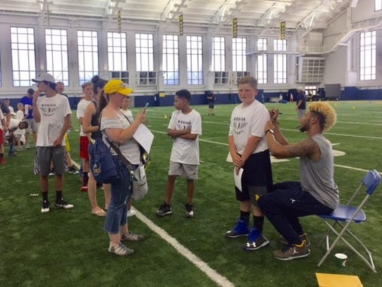 Eddie McDoom signs autographs during Michigan's youth