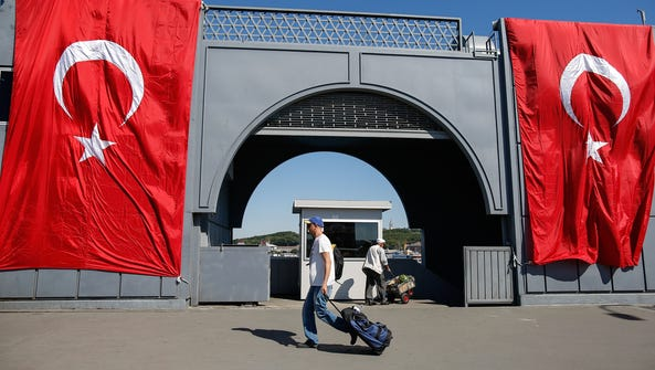 A man walks past Turkish flags in Istanbul on July