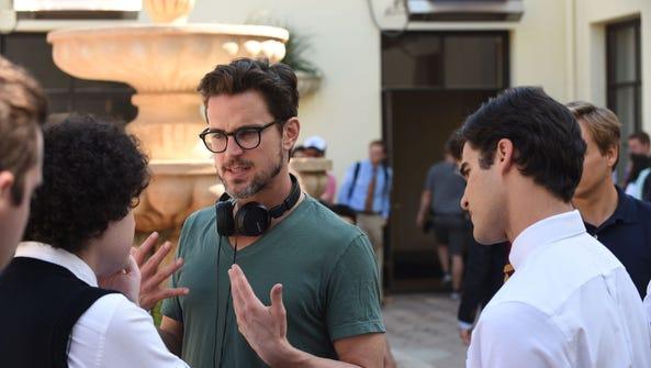 Director Matt Bomer, facing camera, talks to cast and