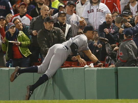 Yankees right fielder Aaron Judge (99) dives into the stands to catch a fly ball hit by Boston Red Sox shortstop Xander Bogaerts (not pictured) during the third inning at Fenway Park.