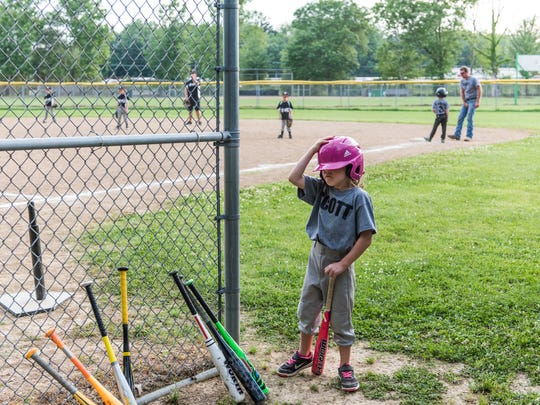 Harper Anderson adjusts her helmet as she waits for her turn to bat during a little league baseball game between the Scott and St. Joe teams at the Scott Township baseball fields in Evansville, Indiana, June 5, 2017.