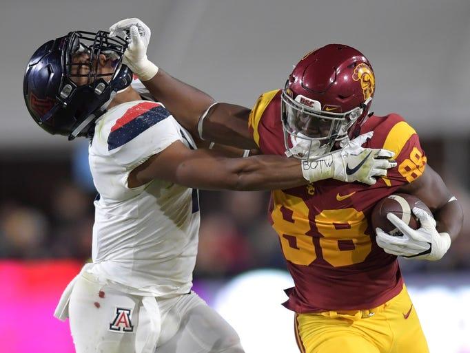 USC's Daniel Imatorbhebhe (88) stiffarms Arizona linebacker
