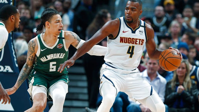 Denver Nuggets forward Paul Millsap, right, works the ball to the basket as Milwaukee Bucks forward D.J. Wilson defends in the second half of an NBA basketball game Monday, March 9, 2020, in Denver.
