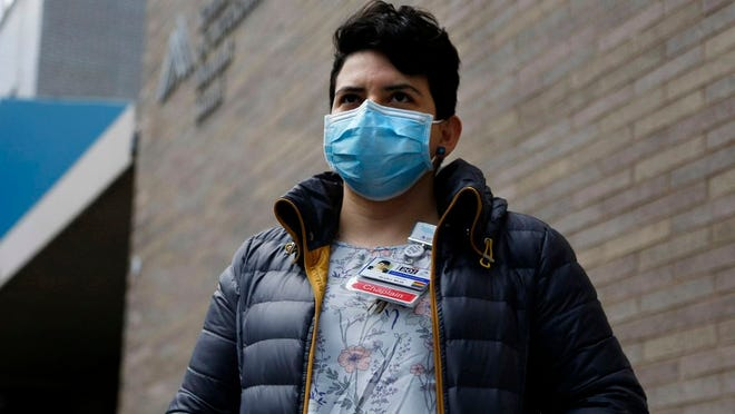 "In this April 16, 2020 photo. Mount Sinai chaplain Silvia Mejia stands outside of the hospital in New York. Mejia, who is one of many young spiritual counselors helping families cope with the coronavirus pandemic, says, ""This feels bigger than a job right now. It feels like a purpose."""