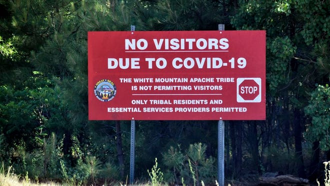In this Thursday, June 25, 2020 photo provided by C.M. Clay, a sign alerts motorists that visitors are not allowed on the Fort Apache Indian Reservation in eastern Arizona. The reservation, home to the White Mountain Apache Tribe, will be under lockdown this weekend to help slow the spread of the coronavirus.