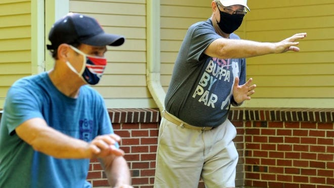 Jim Mandeville of Marshfield, right, follows the lead of Tai Chi instructor Mike Showstack during an outdoor Tai Chi class at the Marshfield Senior Center Monday, Aug. 24, 2020. Tom Gorman/For The Patriot Ledger