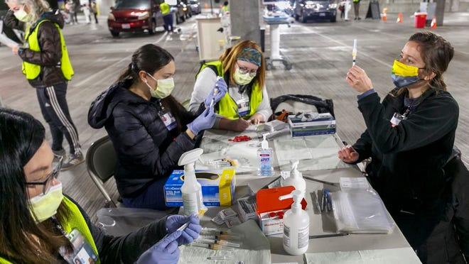 FILE - In this Sunday, Jan. 10, 2021, file photo, Medical professionals from Oregon Health & Science University load syringes with the Moderna COVID-19 vaccine at a drive-thru vaccination clinic in Portland, Ore. The U.S. is entering the second month of the largest vaccination effort in history with a massive expansion of the campaign, opening up football stadiums, major league ballparks, fairgrounds and convention centers to inoculate a larger and more diverse pool of people.