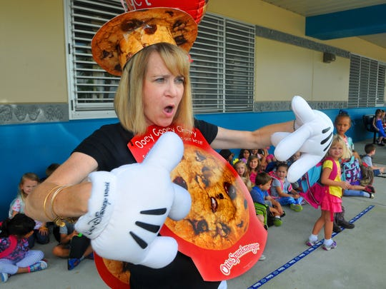 Robyn DeKeyser, a parent volunteer at Manatee Elementary in Viera, greets kindergartners and their parents in the bus loop to promote a PTO fundraiser last fall.
