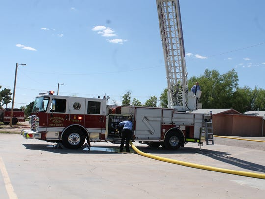 Firefighters demonstrating the adjustable waterway and length of rescue ladder on Fire Truck #2
