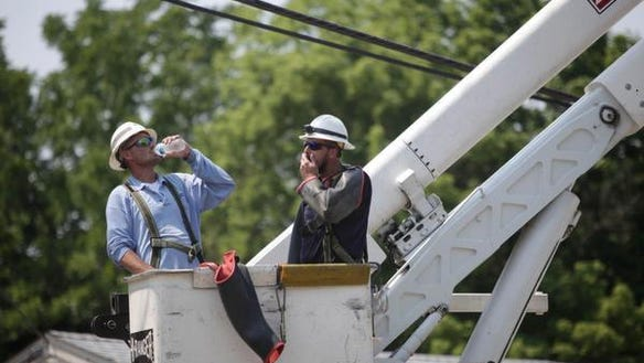 Two Delmarva Power workers take a quick break to hydrate