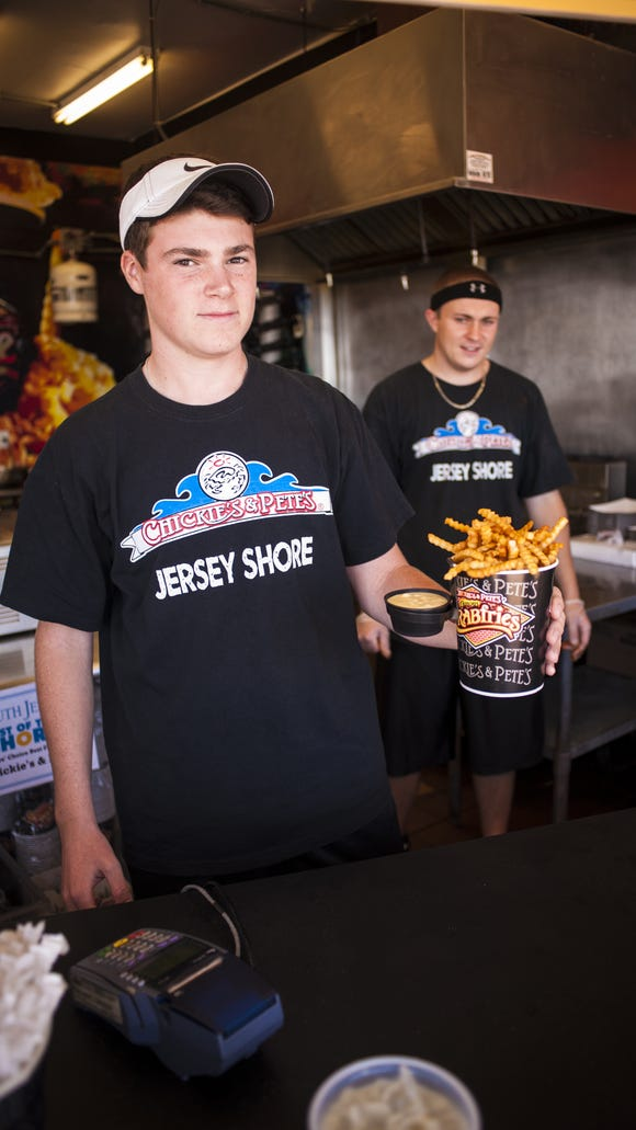 A Chickie's and Pete's worker holds tub of crabfries