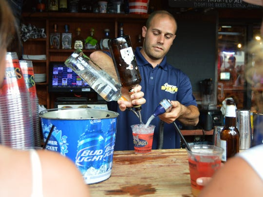 Brian O'Connell, Starboard bartender, prepares an Orange Crush with freshly squeezed oranges.