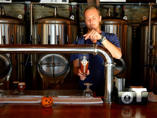 Devin Medd, bartender at Dewey Beer Co., pours The