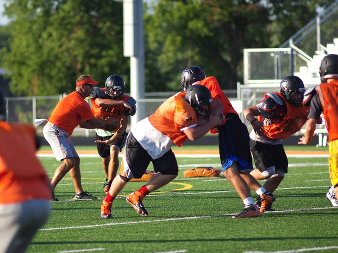 Solon head coach Kevin Miller practices the mesh aspect of the Solon Spartan offense during a controlled scrimmage situation at Solon's practice on Aug. 13, 2014.