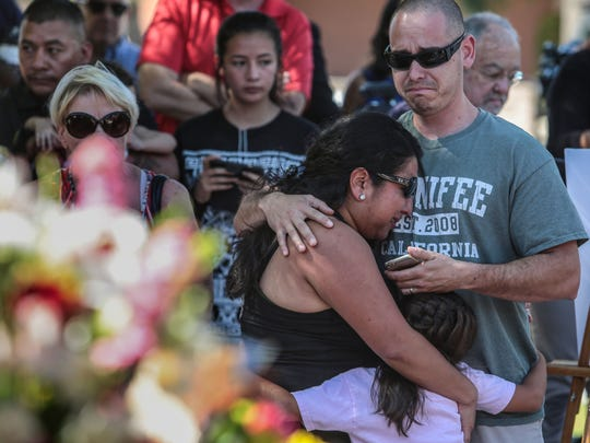 "Mourners cry after placing flowers for fallen Palm Springs Police officers Lesley Zerebny and Jose Gilbert ""Gil"" Vega on the police memorial in front of the Palm Springs Police Department on Sunday, Oct. 9, 2016."