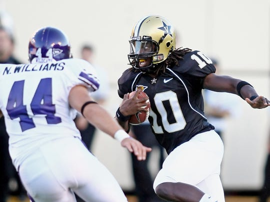 Vanderbilt quarterback Larry Smith, right, look up for a running room as Northwestern's Nate Williams moves in during the first quarter in Nashville, Tenn., Saturday, Sept. 4, 2010.