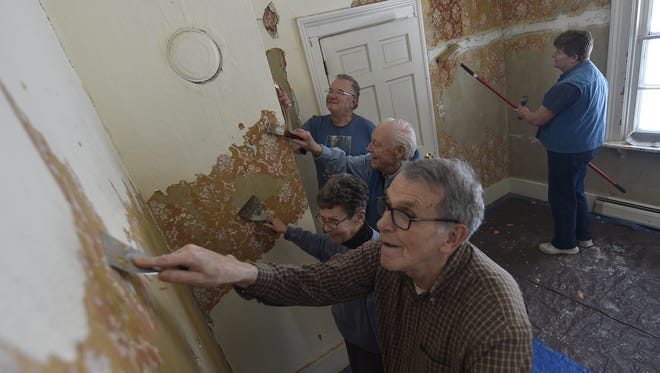 Scrapers in hand, volunteers remove layers of wallpaper at the Upper Range Lighthouse. From left, Pete Grimyser, Sherrill Eichler, Al Eichler, Ed Miller and Sandy Miller. The interior restoration is expected to be completed by late April.