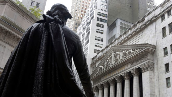FILE - In this Oct. 2, 2014, file photo, the statue of George Washington on the steps of Federal Hall faces the facade of the New York Stock Exchange.