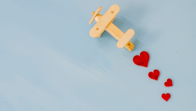 Getty Images A plane flying over a plain background, trailing little hearts as a conceptual Valentine's background.