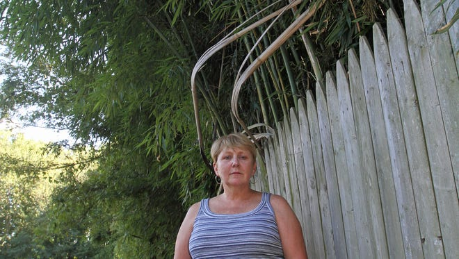 Cynthia Anselmo stands near the yellow groove bamboo in her neighbor's property.