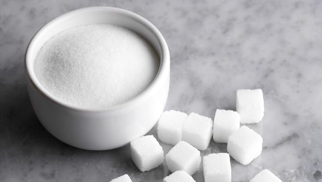 Granulated sugar in bowl with cubes.