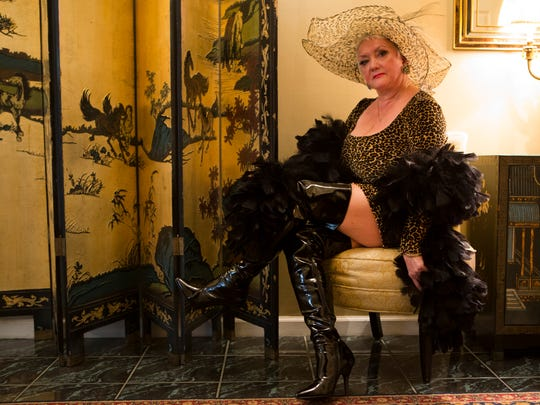 Joyce Bell wears a Cara Bella leopard dress with thigh-high patent leather boots by Pleaser, black ostrich feather stole; and leopard print fabric hat imported from Italy.