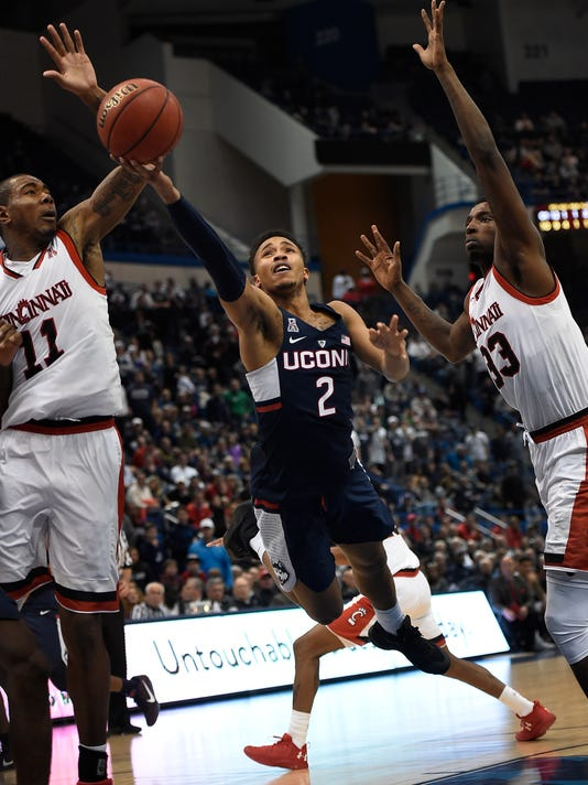Connecticut's Jalen Adams, center shoots between Cincinnati's Gary Clark, left, and Nysier Brooks, right, during the second half of an NCAA college basketball game in the American Athletic Conference tournament semifinals, Saturday, March 11, 2017, in Hartford, Conn. (AP Photo/Jessica Hill)