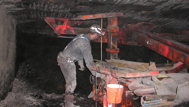 A coal miner puts bolts up to support a mine roof in eastern Kentucky.