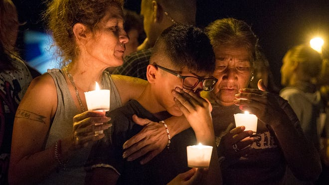 Mona Rodriguez holds her 12-year-old son, J. Anthony Hernandez, during a candlelight vigil held for the victims of a fatal shooting at the First Baptist Church in Sutherland Springs, Texas, on Nov. 5, 2017.