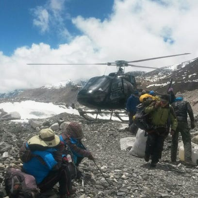 A rescue chopper lands carrying people from higher camps to Everest Base Camp in Nepal on Monday.
