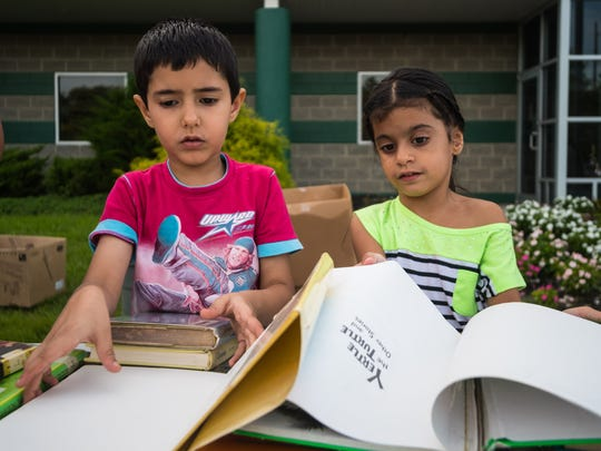 Yourah Singh, 7, and Gurleen Kahn, 5, sort through a pile of books during Vineland School District's book giveaway at the Vineland School District Warehouse on Wednesday, August 30.