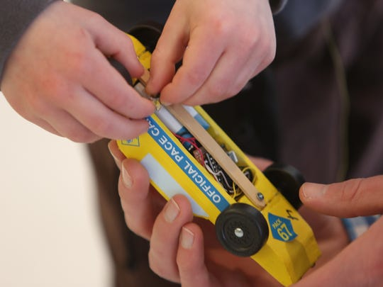"Participants examine a tricked-out pinewood derby car from the ""Daddy Derby."""