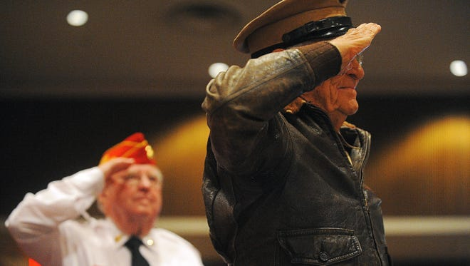Claude Hone, 95, right, a Marine Corps World War II fighter pilot, and Gene Cordes, a Marine Corps veteran, stand and salute during the Military and Veterans Affairs Committee of the Sioux Falls Area Chamber of Commerce's Veterans Day program Wednesday, Nov. 11, 2015, at Lincoln High School in Sioux Falls.