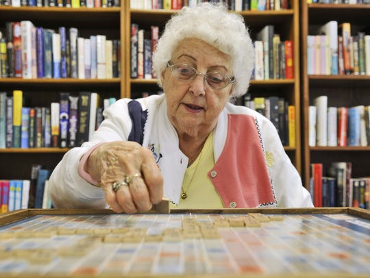 Mary Ann Poepping lays down a tile during a game of