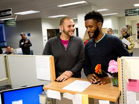 Derek Daniels, left, 25, and Christian Montgomery, 28, were the first couple in line at the Lee County clerk of courts office to receive a license for marriage Tuesday.