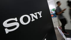 Visitors walk past a logo of Sony at Sony Building