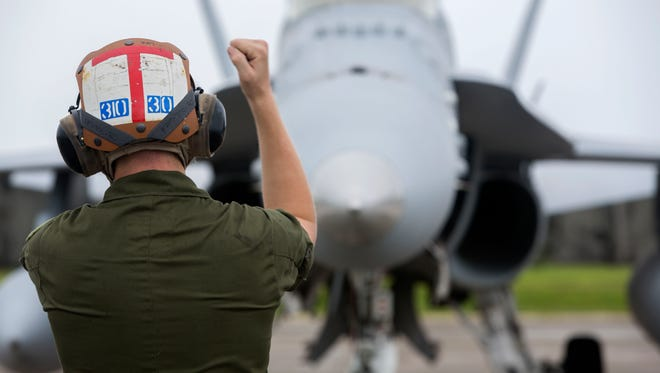 A U.S. Marine with Marine All-Weather Fighter Attack Squadron 533, 2nd Marine Aircraft Wing, signals an FA-18 Hornet into the flight line on Andersen Air Force Base, Guam, Sept. 17, 2014 during Exercise Valiant Shield 14. Valiant Shield 14 is a biennial U.S. forces only exercise focusing on engaging units at sea, on land, and in cyberspace in response to a range of mission areas.