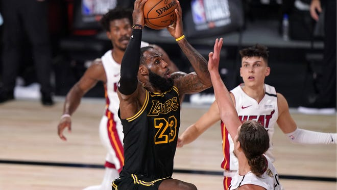 Los Angeles Lakers forward LeBron James (23) goes up for a shot in front of Miami Heat's Kelly Olynyk, right front, as Jimmy Butler, left rear, and Tyler Herro, right rear, look on during the second half of Game 2 of basketball's NBA Finals, Friday, Oct. 2, 2020, in Lake Buena Vista, Fla.