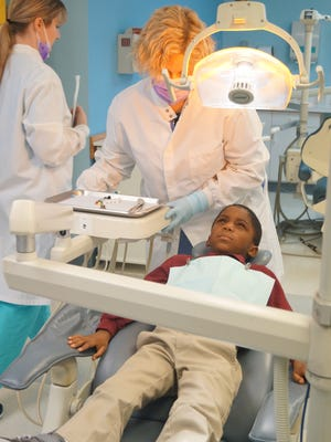 Sandra Cortes, a registered dental hygienist at CompleteCare, prepares for her visit with Ja'Tron Gardner, 6, a student at Cherry Street School, as part of the Smile Start program.