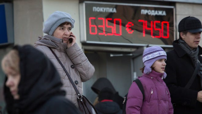 People walk past an electronic display board indicating the euro-to-ruble exchange rate outside a currency exchange office in St. Petersburg, Russia.