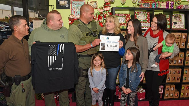 Angel Rice, Owner of Under the Carolina Moon, presents a check to K-9 Officer Brandon Surratt. The money will go toward a new K-9 for Anderson County.