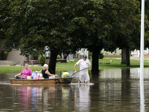 David Dixon pulls Heather Dixon and Dawn Suhr  in a boat down Main Street in Rock Valley Tuesday afternoon after pulling some valuables out of their flooded houses, June 17, 2014.