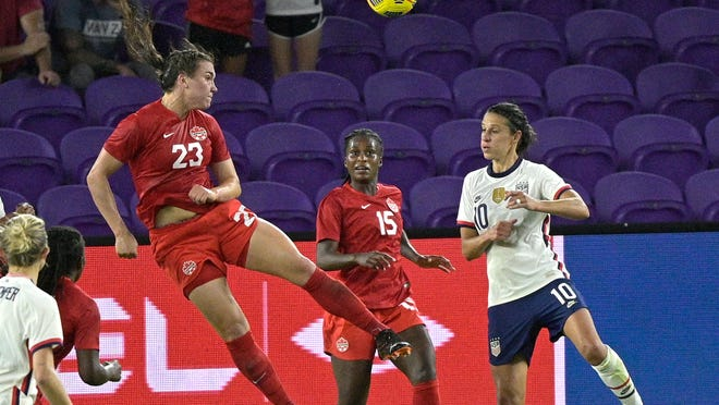 Canada defender Vanessa Gilles (23) heads the ball in front of forward Nichelle Prince (15) and United States forward Carli Lloyd (10) during the first half of a SheBelieves Cup women's soccer match, Thursday, Feb. 18, 2021, in Orlando, Fla. (AP Photo/Phelan M. Ebenhack)