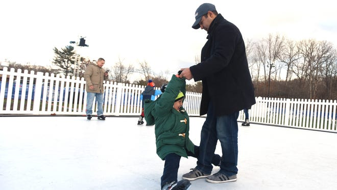 Michael Ruiz of Oradell helping six-year-old son, Lucas on the beginner's ice rink on Saturday, Dec. 3, 2016. Bergen County residents enjoying Winter Wonderland, the new attraction created by the Bergen County administration that's meant to provide residents with family-friendly holiday fun.
