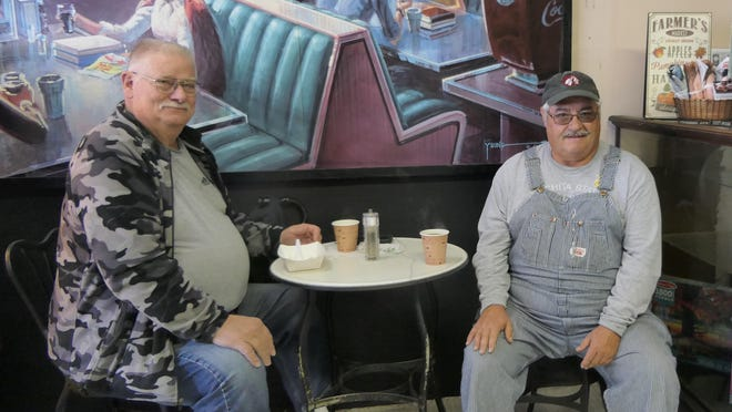 Kenneth and Art Mayfield drink coffee and eat their lunch at City Sundries in Marquette.