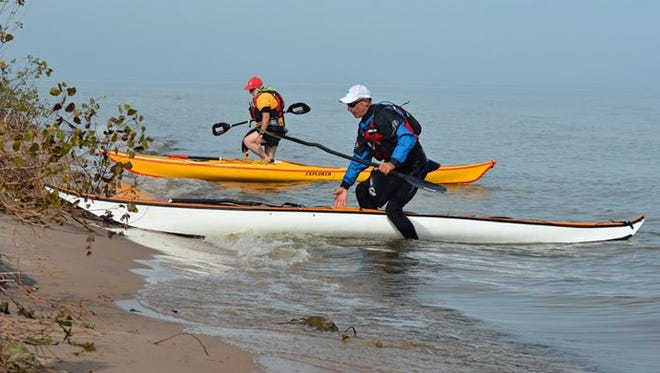 John Browning and Russell Johnson beach their sea kayaks at Point Beach State Forest where two new water-access campsites were unveiled Wednesday, Sept. 24, 2014.