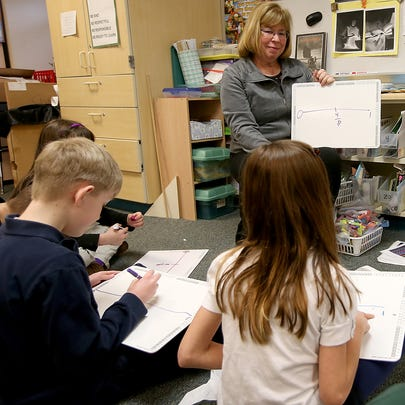 Teacher Bev Godfrey works on fractions with students