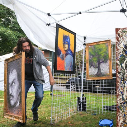 Artist Billy Tackett of Florence, Ky. sets up his booth